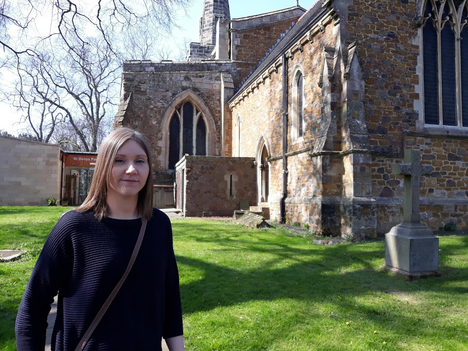 A picture of Sarah standing outside the church